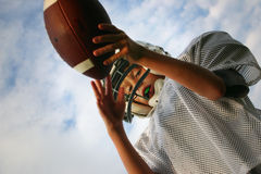 Pass Interception. Picture shot from below of boy catching a football Royalty Free Stock Photos