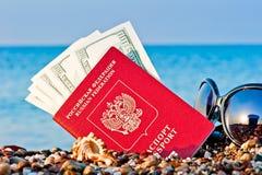 Pass mit Geld und Sonnenbrille auf dem Strand Stockbilder