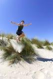 Pass-Sitz, gesunder mittlerer gealterter Mann, der über Sanddünen springt Lizenzfreie Stockfotografie