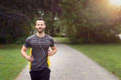 Passa den skäggiga unga mannen som joggar till och med en parkera royaltyfri bild