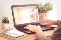 Passa il computer portatile di battitura a macchina con il fondo della sfuocatura sullo schermo, filt d'annata Immagine Stock