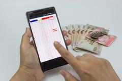 Passa la donna che per mezzo dello smartphone con soldi su fondo bianco Fotografie Stock