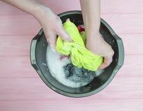 Passa a vestiti del femalewash la famiglia casuale sporca in un fare del bacino domestico Fotografie Stock Libere da Diritti