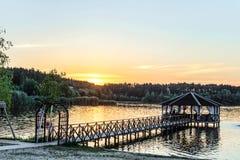 Passadiço com um miradouro na costa do lago à luz do baixo sol da noite Fotografia de Stock