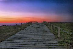 The passage. A beautiful sunset on a footbridge to the beach Royalty Free Stock Photography