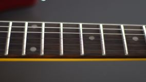 Passage along the strings on an electric guitar close-up stock footage