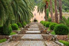 Passage couvert droit de jardin avec des pavés ronds Photos libres de droits