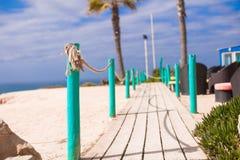 Passage couvert en bois à la plage sablonneuse Photographie stock