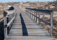Passage couvert en bois avec la balustrade par des dunes de sable à l'île de prune Images libres de droits