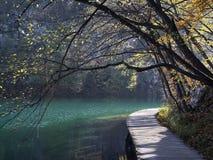 Passage couvert en bois le long du rivage du lac et des arbres d'automne Pli Photographie stock libre de droits
