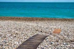 Passage couvert en bois menant à la mer sur un Pebble Beach Photographie stock libre de droits