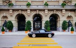 Passage de luxe noir de course de voiture de sport par des portes de voûte de Parliamen suisse photo stock