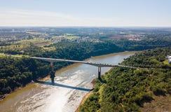 Passage de pont et de frontières en pont de Fraternity au-dessus de la rivière d'Iguassu et de la ville de Puerto Iguazu L'Argent images libres de droits