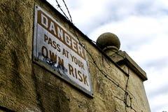 Passage de signe de danger à vos risques et périls photographie stock