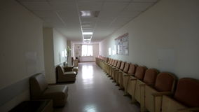 Passage through an empty corridor. The camera moves through the empty corridor of the clinic to the light. There is a bright light at the end of the corridor stock video footage