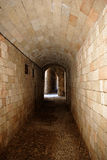 Passage. Empty stone passage inside old medieval fortress lit by sun at end Stock Photo