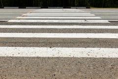 Passage pour piétons blanc à travers la route Image stock