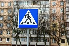 Passage pour piétons de panneau routier sur le fond des arbres et d'un bâtiment à plusiers étages Images libres de droits