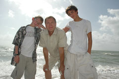 Passage of Time. A grandfather stands with his grandsons on the beach. Family spending time together Stock Images