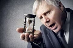 The Passage of Time. Old businessman looking at an hourglass Stock Image