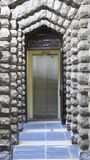 Passage to elevator. Historic passage made of stones to a modern elevator. Photo taken at Vortrekker Monument, close to Pretoria, South Africa Stock Photo