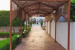 Passage to the pool under a wooden gazebo royalty free stock photography
