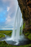 The passage between waterfall and rock. The warm July day in Iceland. Seljalandsfoss waterfall Stock Photography