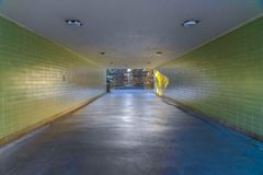 Passage way under a building with cracked floor and brick wall royalty free stock image