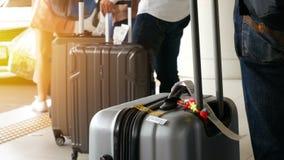 Passageiro com a bagagem grande do rolo que está na linha fila de espera do táxi no parque de estacionamento do táxi no terminal  filme