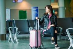 Passageiro da linha aérea em um avião de espera do voo da sala de estar do aeroporto Mulher caucasiano com o smartphone na sala d imagens de stock royalty free
