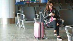 Passageiro da linha aérea em um avião de espera do voo da sala de estar do aeroporto Mulher caucasiano que procura o tempo na sal filme