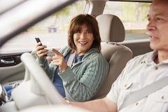 Passageiro da mulher que usa GPS no smartphone em apontar do carro fotos de stock royalty free