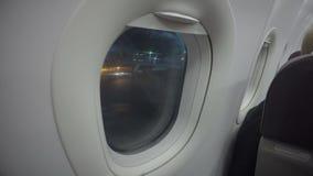 Passageiro do avião que olha através da janela plana no aeroporto Atraso de voo da noite vídeos de arquivo