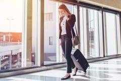 Passageiro fêmea de sorriso que continua à porta de saída que puxa a mala de viagem através do ajuntamento do aeroporto ao falar  imagens de stock royalty free