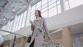 Passageiro fêmea novo no aeroporto, com seu tablet pc ao esperar seu voo andando no terminal video estoque