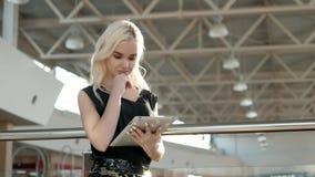 Passageiro fêmea novo no aeroporto usando seu tablet pc ao esperar o voo, mulher bonita da menina dentro Foto de Stock