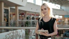Passageiro fêmea novo no aeroporto usando seu tablet pc ao esperar o voo, mulher bonita da menina dentro Foto de Stock Royalty Free