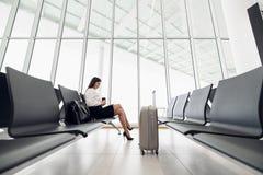 Passageiro f?mea novo no aeroporto, usando seu tablet pc ao esperar seu voo foto de stock