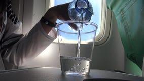 passageiro 4K novo asiático na água plana da bebida durante o voo vídeos de arquivo