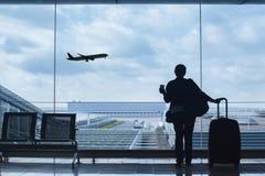 Passageiro no aeroporto que olha a descolagem dos aviões imagens de stock