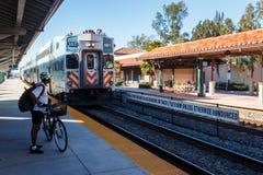 Passageiro no capacete com esperas da bicicleta para o tri trem do trilho na plataforma da estação de Hollywood imagens de stock