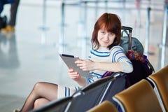 Passageiro novo no aeroporto, usando sua tabuleta imagem de stock