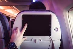 Passageiro plano no avião usando o tablet pc fotos de stock