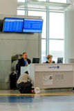 Passageiro que inquire de um representante da linha aérea em um a moderno Imagem de Stock Royalty Free