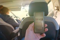 Passageiro que usa o app esperto do telefone para avaliar um táxi ou um par moderno para espreitar motorista ridesharing fotografia de stock