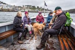 Passageiros a bordo da balsa de passageiro pequena através do porto de Fowey em Fowey, Cornualha, Reino Unido foto de stock royalty free