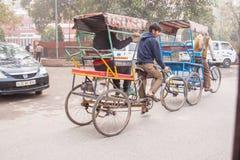Passageiros das balsas de um homem em um pedicab através das ruas nevoentas foto de stock
