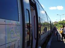 Passageiros e trem da periferia durante horas de verão fotos de stock royalty free