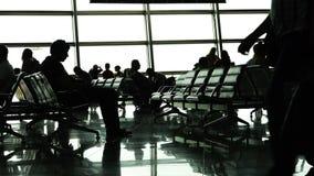 Passageiros em à espera esperando seu voo no salão do aeroporto vídeos de arquivo
