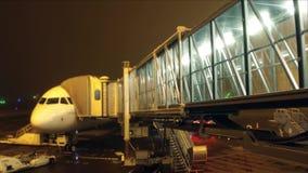 Passageiros irreconhecíveis que embarcam o avião de passageiros usando a ponte de vidro do jato na noite Curso, partida, deixando filme